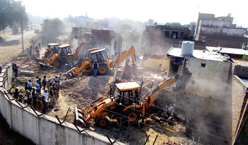 MCG (Municipal Corporation Gurgaon) bulldozers demolish illegal structures built near ammunition depot in Gurgaon on Dec 3, 2014.