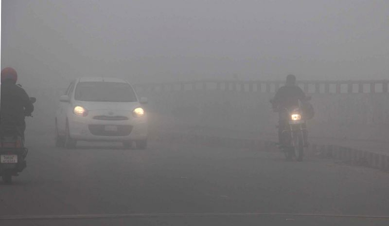 Vehicles ply with their headlights switched-on as a blanket of dense fog covers the National Highway - 8 in Gurgaon, on Dec 16, 2014.