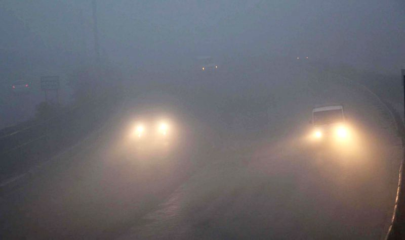 Vehicles ply with their headlights switched-on as dense fog covers Gurgaon, on Dec 25, 2014.