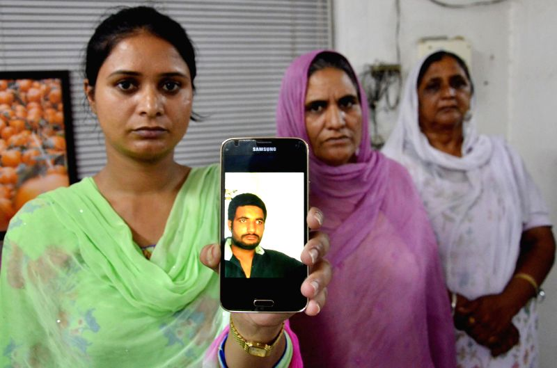 Gurpreet Kaur shows a photograph of her brother Manjinder Singh who is believed to be trapped in the violence-hit Iraqi city of Mosul, in Punjab on June 18, 2014. - Gurpreet Kaur and Manjinder Singh