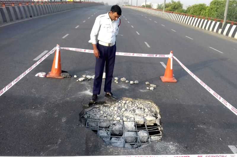 Gurugram: A traffic police officer inspects a large four feet hole which appears on the Hero Honda Chowk flyover on the Delhi-Jaipur stretch of the National Highway 8, in Gurugram, on May 8, 2019. (Photo: IANS)