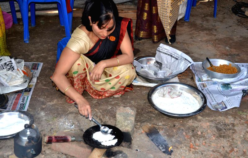 A lady makes `pitha` (sweetmeat) during a Bhogali Bihu exhibition, organised by Chiro Seuj Kala Kristi Kendra at Lakhadhar Bora Khetra in Guwahati on Jan 9, 2015.