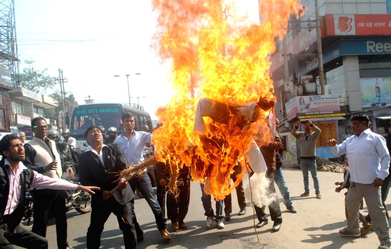 AGP activists burning the effigy of PM Narendra Modi as a protest against BJP`s vision document for the Delhi assembly polls which mentioned the people from north eastern states living in .. - Narendra Modi