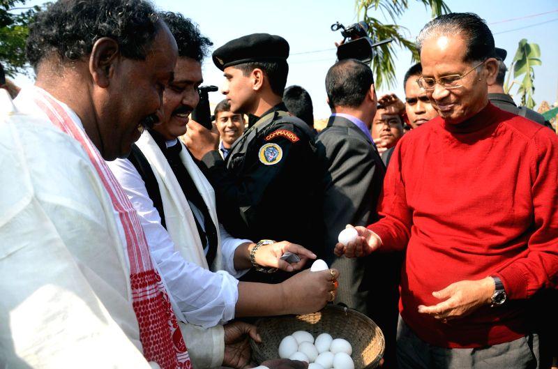 Assam Chief Minister Tarun Gogoi tries his hands at the traditional egg fight during the Bhogali Utsav 2015 organised by Assam Tourism at Sarusajai Stadium in Guwahati on Jan 18, 2015. - Tarun Gogoi