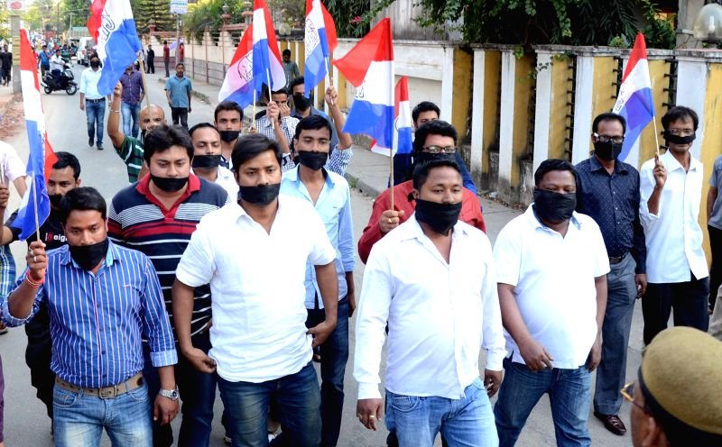 Assam Gana Parishad (AGP) workers tie their mouth with black bands as they stage a demonstration against the brutal killing of an Assamese man in Dimapur, in Guwahati on March 7, 2015.