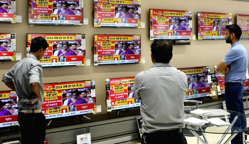 Guwahati: People busy watching the telecast of Union Budget 2019 presented by Union Finance Minister Nirmala Sitharaman in the Lok Sabha; at an electronics showroom in Guwahati on July 5, 2019.
