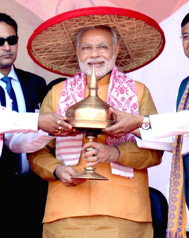 Prime Minister Narendra Modi being felicitated with `Japi` and `Sorai` during a BJP meeting at Indira Gandhi Athletic Stadium in Guwahati on Nov 30, 2014. - Narendra Modi