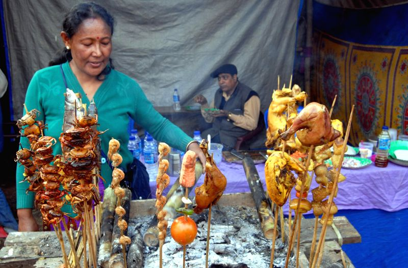 Women prepare traditional food during Bhogali Bihu Mela in Guwahati on Jan 10, 2015.