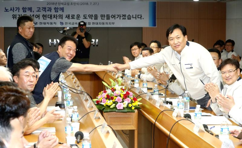 Ha Eon-tae (R), a vice president of Hyundai Motor Co., shakes hands with the carmaker's union leader, Ha Bu-young, during a ceremony at its plant in Ulsan, 414 kilometers southeast of Seoul, ...