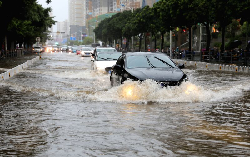 HAIKOU, Aug. 10, 2018 - Cars run through the floodwater in Haikou, south China's Hainan Province, Aug. 10, 2018. Hainan was hit by heavy rainfalls under the influence of a tropical depression on ...