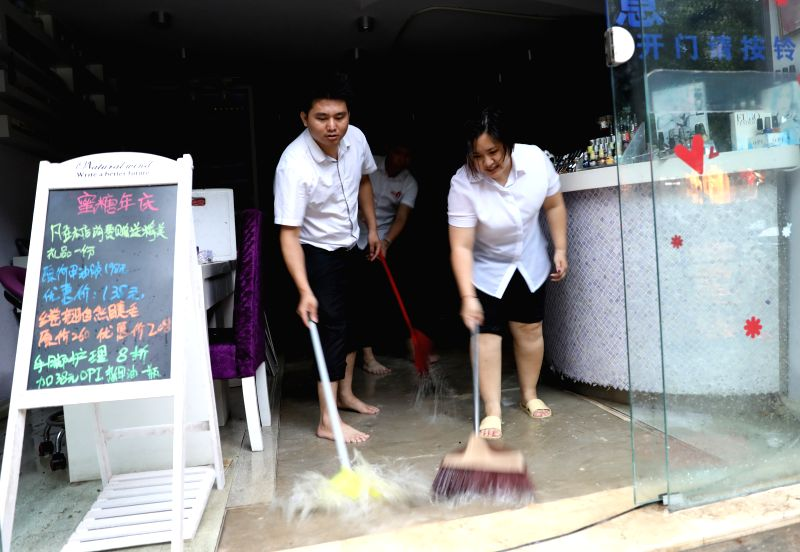 HAIKOU, Aug. 10, 2018 - Staff of a shop drain the floodwater in Haikou, south China's Hainan Province, Aug. 10, 2018. Hainan was hit by heavy rainfalls under the influence of a tropical depression on ...