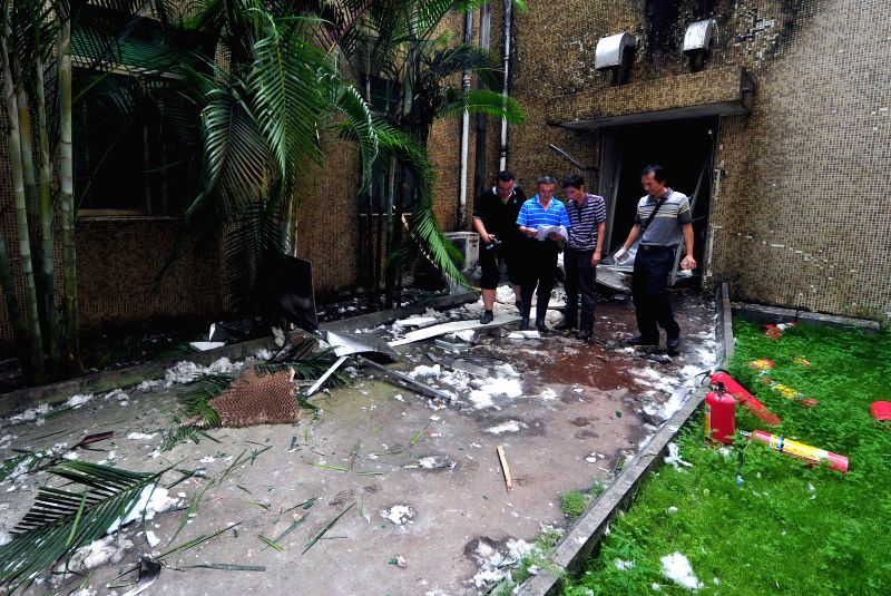 Staff members investigate the site where a blast occurred in Hainan Huigu Pharmaceutical Co., Ltd., Haikou, capital of south China's island province Hainan, July 1, ..