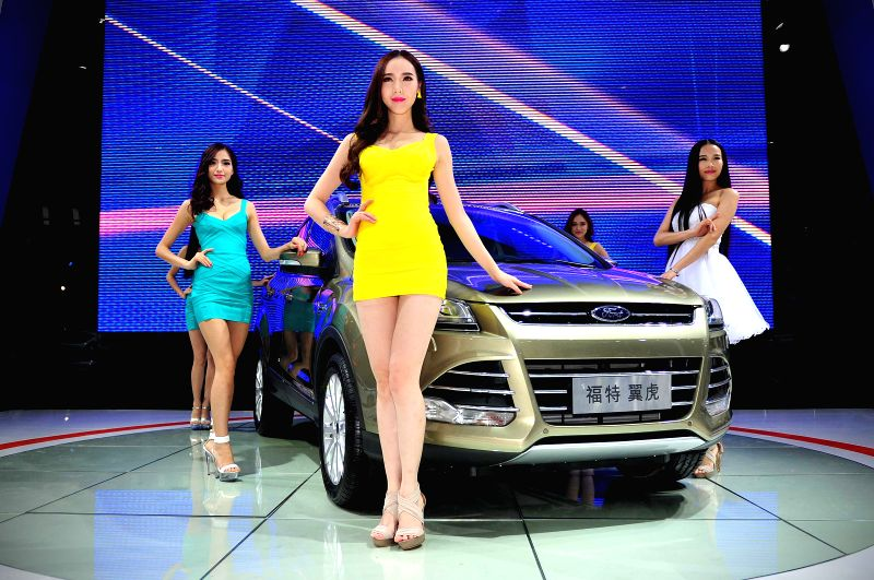 A model presents a car at the 2014 China Hainan International Automotive Exhibition in Haikou, capital of south China's Hainan Province, July 10, 2014. The four-day .