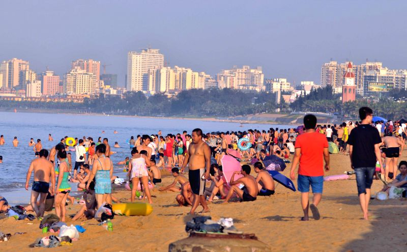 People cool off on the beach in Haikou, capital of south China's Hainan Province, May 14, 2014. A heat wave hit the island province these days, with the highest ...