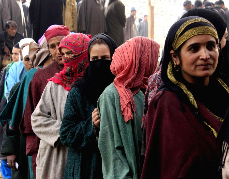Women queue-up outside a polling booth in Hajjan village to cast their votes during the first phase of Jammu and Kashmir polls in Baramulla district of the state on Nov 25, 2014.