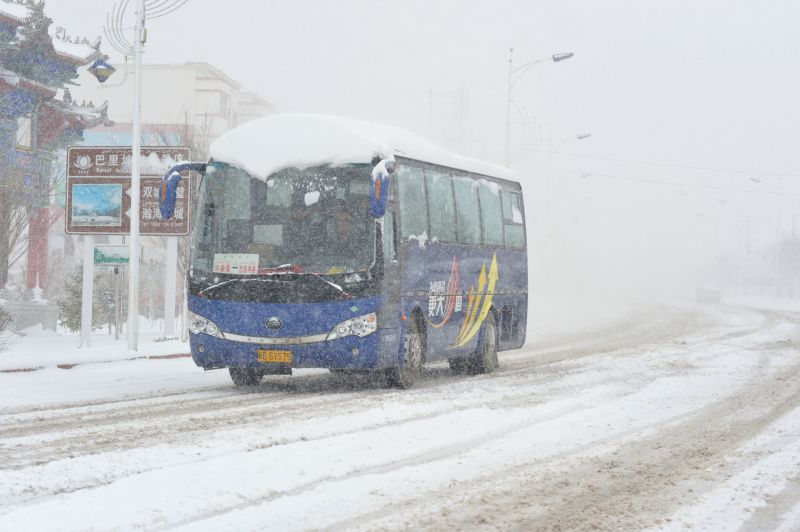 A bus runs in snow at Kazak Autonomous County of Barkol in Hami, northwest China's Xinjiang Uygur Autonomous Region, April 17, 2014. A snowfall hit the county on ...