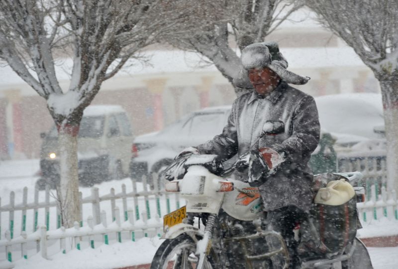 An old man rides in snow at Kazak Autonomous County of Barkol in Hami, northwest China's Xinjiang Uygur Autonomous Region, April 17, 2014. A snowfall hit the county ..