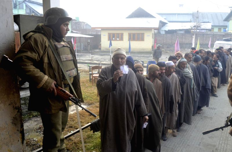 A soldier stands guard at a polling booth as people queue-up to cast their votes during the second phase of assembly polls in Handwara, Kupwara district, Jammu and Kashmir on Dec 2, 2014.