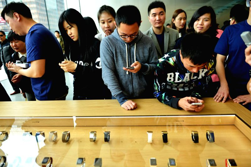 Customers look at Apple Watches at an Apple store in Hangzhou, capital of east China's Zhejiang Province, April 10, 2015. The Apple Watch made its debut Friday. ...