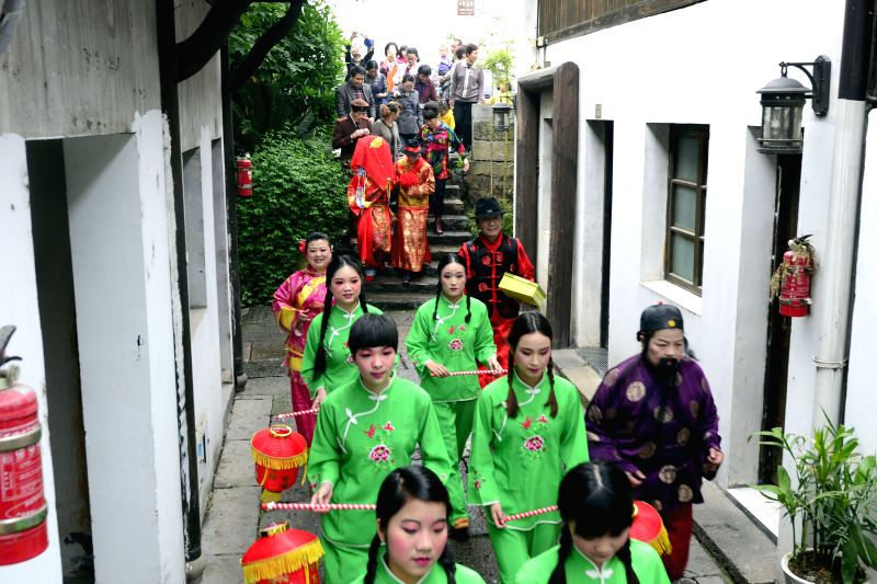 The newlyweds, their families, and companions walk to bridegroom's house, in a historical area of Hangzhou, capital of east China's Zhejiang Province, April 26, .
