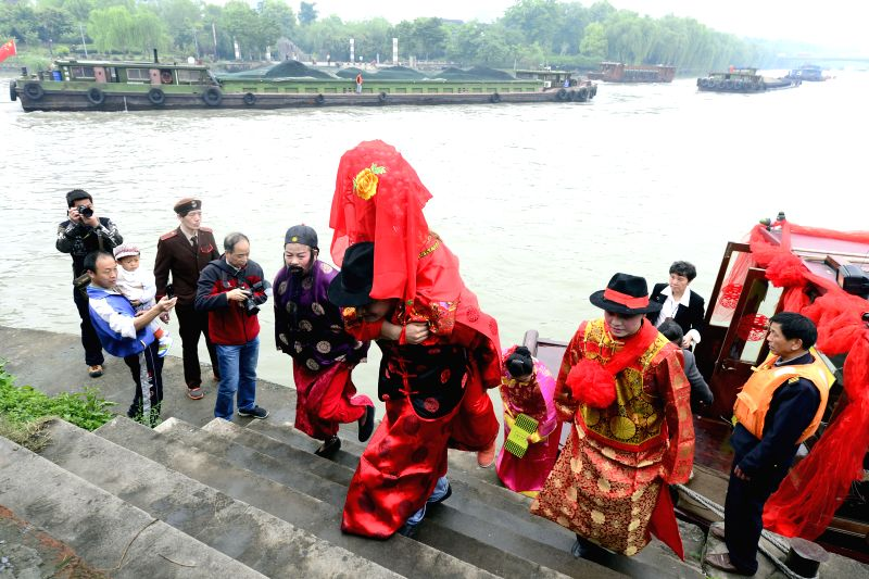 The newlyweds, their families, and companions get off a ship and head for bridegroom's house, in a historical area of Hangzhou, capital of east China's Zhejiang .