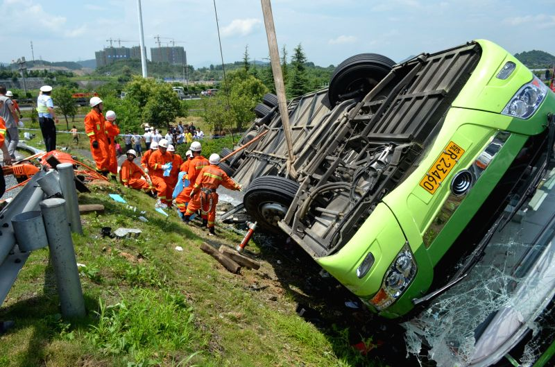 Rescuers work on the scene of a passenger coach rollover accident along the Hangzhou-Huizhou highway in Hangzhou, capital of east China's Zhejiang Province, July ..