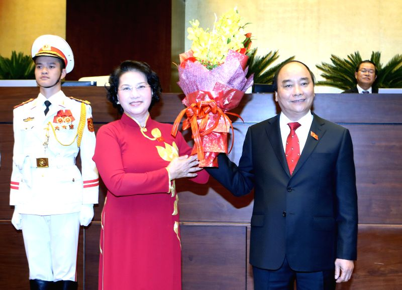 HANOI, April 7, 2016 - Vietnamese National Assembly Chairperson Nguyen Thi Kim Ngan presents a bouquet of flowers to Nguyen Xuan Phuc after he was elected as the country's prime minister in Hanoi, ...
