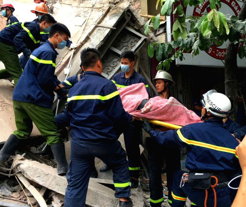 HANOI, Aug. 4, 2016 - An injured person is rescued from the collapsed building in Hanoi, capital of Vietnam, Aug. 4, 2016. A four-storey building in Vietnam's capital Hanoi collapsed on Thursday ...