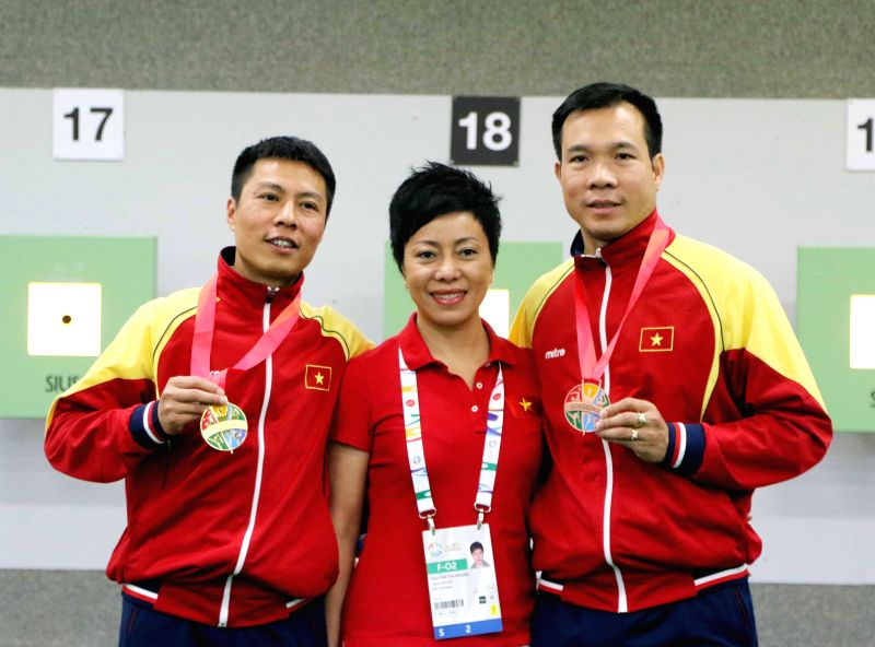 HANOI, Aug. 9, 2016 - File photo taken on June, 2015 shows Vietnamese marksman Hoang Xuan Vinh (R) poses for group photo with Coach Nguyen Thi Nhung (C) and a teammate after winning medals at the ...