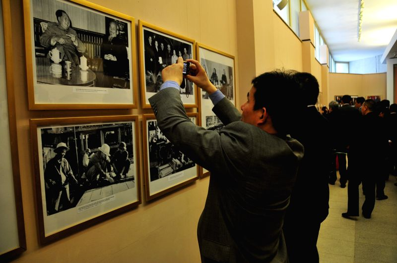 Visitors watch and take photos of pictures displayed at the photo exhibition in Ho Chi Minh Museum in Hanoi, Vietnam, Jan. 19, 2015. A photo exhibition was held ...