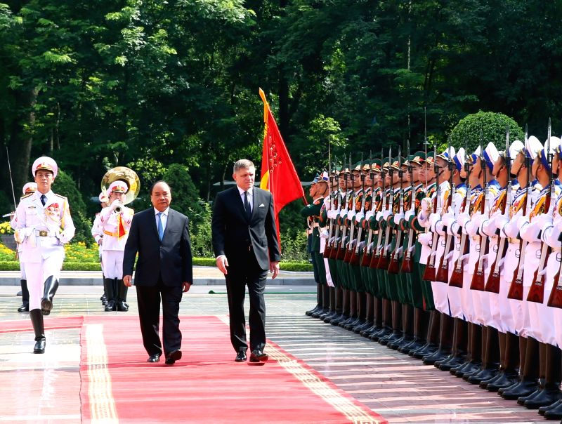 HANOI, July 18, 2016 - Vietnamese Prime Minister Nguyen Xuan Phuc (L, C) and Slovak Prime Minister Robert Fico (R, C) review guard of honor of Vietnam People's Armed Forces in Hanoi, capital of ... - Nguyen Xuan Phuc