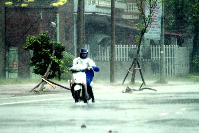 A local resident drives his motorcycle in heavy rain brought by typhoon Rammasun in Mong Cai city, Quang Ninh province, Vietnam, on July 19, 2014. Two houses were ...