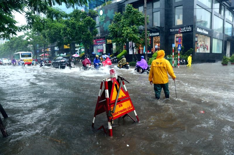 HANOI, July 21, 2018 - People wade through flood after heavy rain brought by Typhoon Son Tinh in Hanoi, capital of Vietnam, July 21, 2018.
