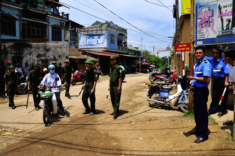 The entrance to the village where a helicopter crash occured has been cordoned off on the outskirts of Hanoi, capital of Vietnam, July 7, 2014. A military helicopter ..