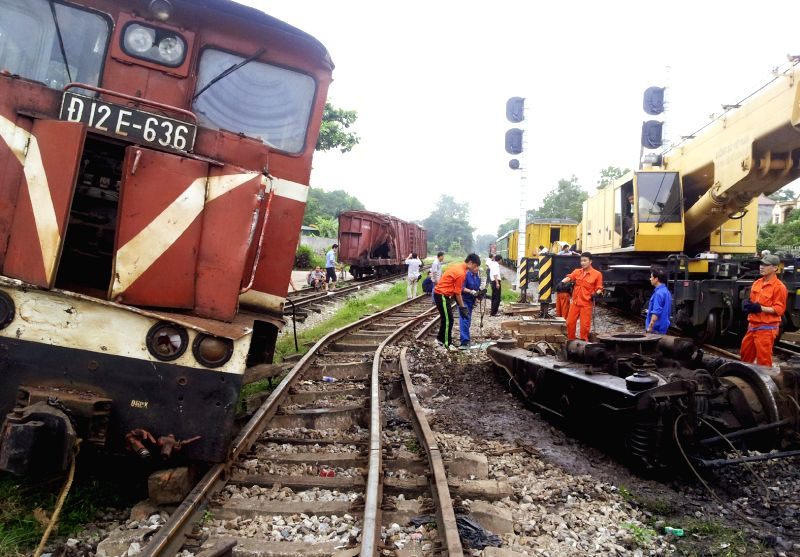 People work at the site of a train accident in Vietnam's northern Thai Nguyen province, June 26, 2014. The accident happened on Wednesday evening when a cargo train ..
