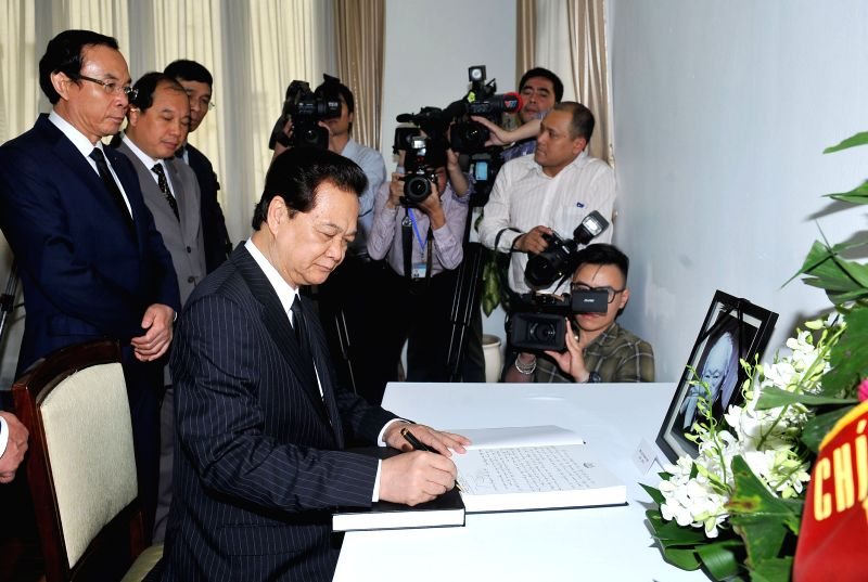Vietnamese Prime Minister Nguyen Tan Dung (front) writes on a condolence book for former Singaporean Prime Minister Lee Kuan Yew at the Singaporean Embassy in ... - Nguyen Tan Dung