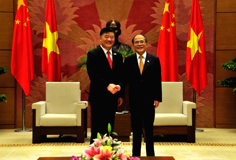 Vietnam's National Assembly Chairman Nguyen Sinh Hung (R) shakes hands with Chen Zhu, Vice Chairman of the Standing Committee of the National People's Congress of ...