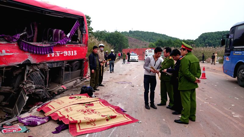 Police work at the site of a traffic accident in Quang Ninh province, north Vietnam, Dec. 16, 2014. Six people died and eight others injured while a coach collided with a container truck in ...