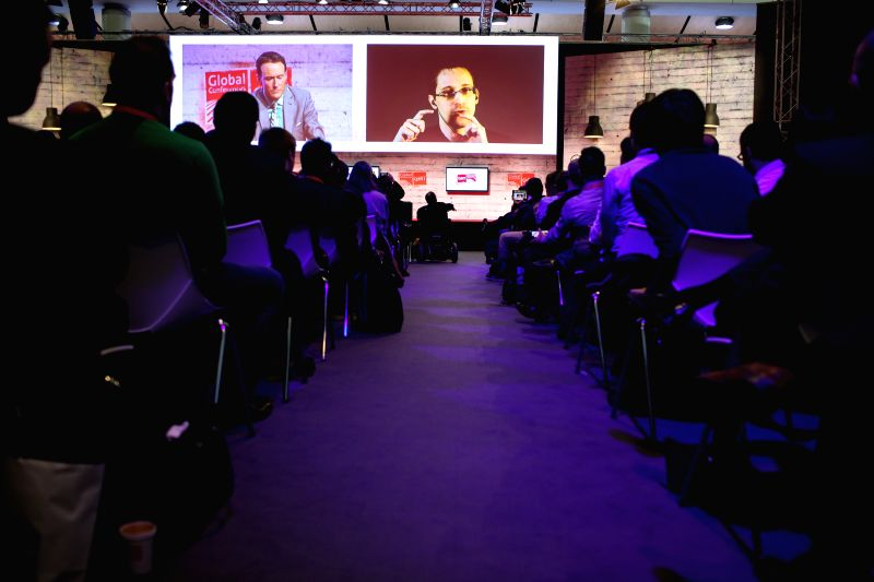 Edward Snowden is seen on the screen during a live remote interview at CeBIT 2015, the world's top trade fair for information and communication technology, in ...