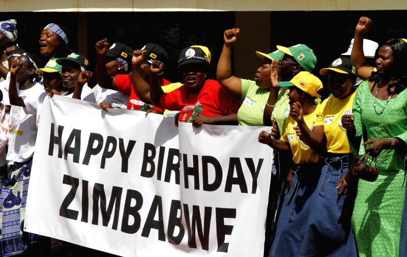 """Zimbabweans uphold a banner saying """"Happy Birthday, Zimbabwe"""" at a grand ceremony held at the National Sports Stadium, in the west suburbs of Harare, ..."""