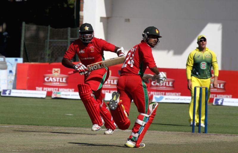 Sikandar Raza Butt (C) and Hamilton Masakadza (L) of Zimbabwe compete during a Triangular series cricket match against Australia at Harare Sports club, on Aug. 25, ..