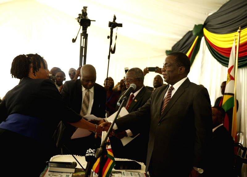 HARARE, Feb. 1, 2018 - Zimbabwean President Emmerson Mnangagwa (R, front) shakes hands with newly appointed Zimbabwe Electoral Commission chairperson Priscilla Chigumba (L, front) during the ...