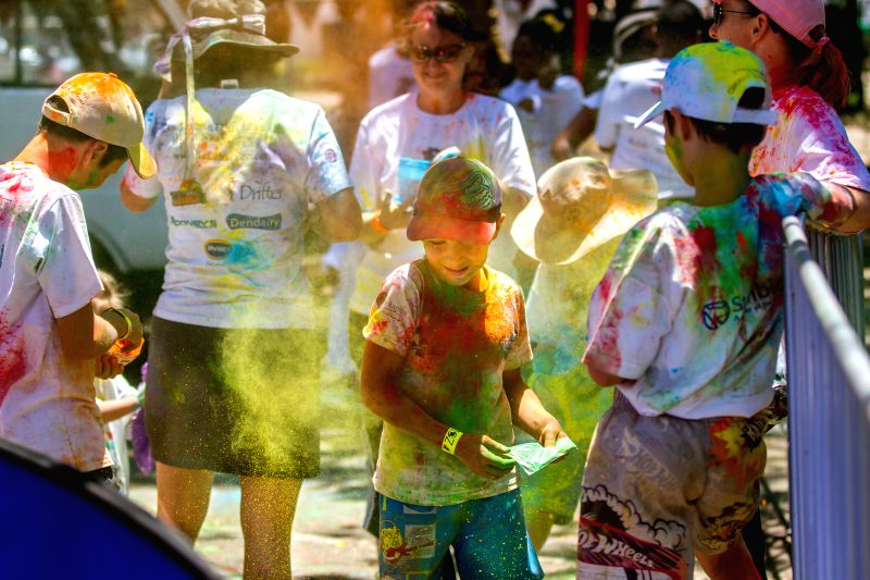 People splash paints onto each other during the Color Run in Harare, Zimbabwe, Dec. 6, 2014. The five-kilometer un-timed race is held to promote healthy living and benefit charity. ...