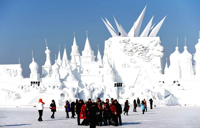 Tourists pose for photos in front of a snow sculpture at the Sun Island International Snow Sculpture Art Expo in Harbin, capital of northeast China's Heilongjiang ...