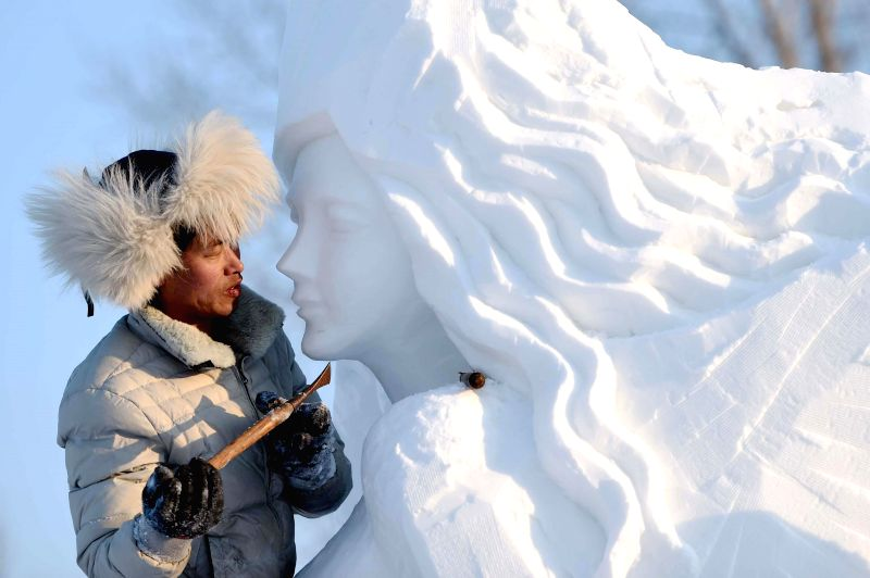 A worker creats a snow sculpture at the Sun Island Park in Harbin, capital of northeast China's Heilongjiang Province, Feb. 5, 2015.