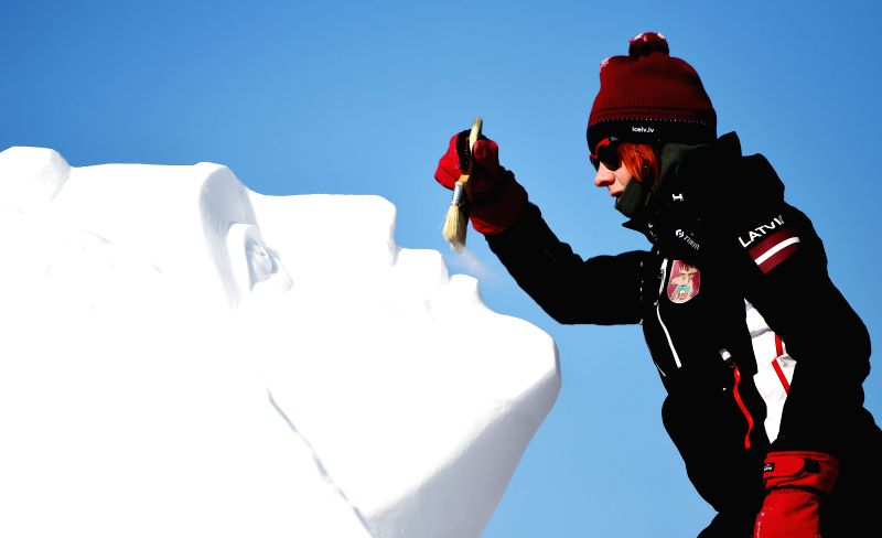 A Latvian sculptor works on a snow sculpture during the 20th Harbin International Snow Sculpture Contest in Harbin, capital of northeast China's Heilongjiang ...