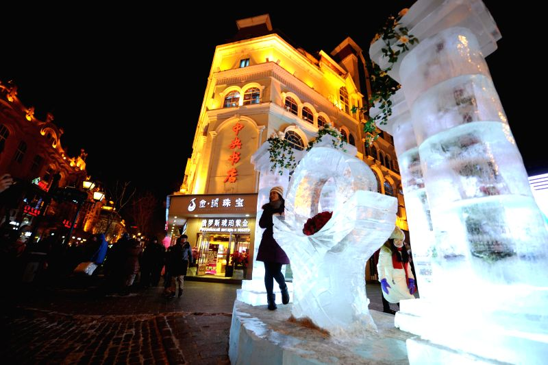 A tourist poses with an ice sculpture at the Central Street of Harbin, capital of northeast China's Heilongjiang Province, Jan. 2, 2015. The 31th International Ice ...