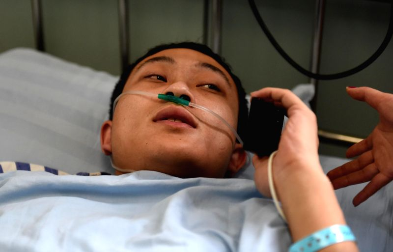 Firefighter Zhang Yu, who was injured in a warehouse blaze, answers phone calls of his friends at a hospital in Harbin, capital of northeast China's Heilongjiang ...