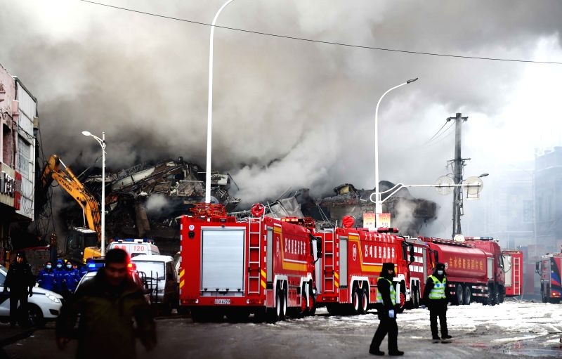 Smokes rise from a collapsed warehouse at the Beifangnanxun ceramics market in Harbin, capital of northeast China's Heilongjiang Province, Jan. 3, 2015. The fire ...