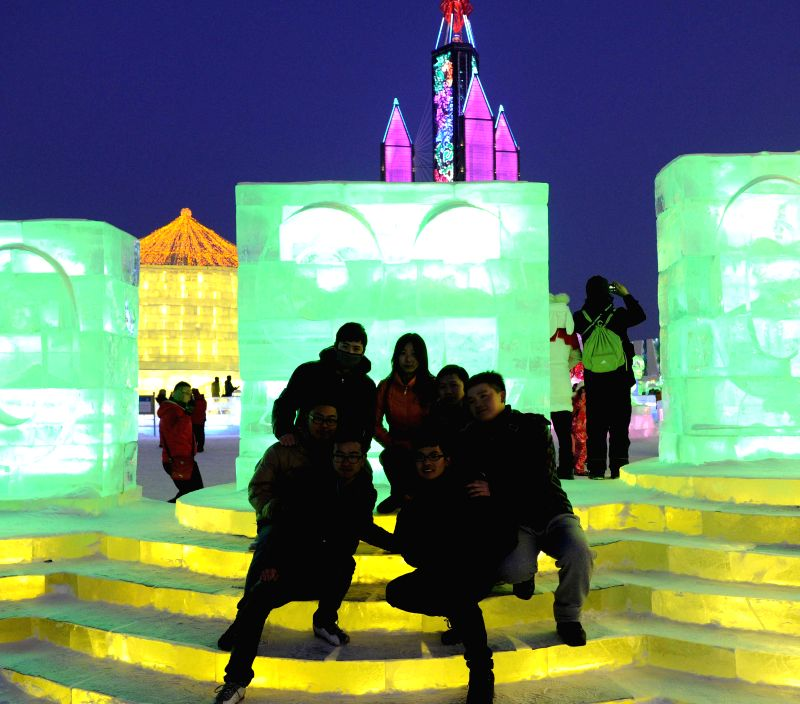Tourists pose for a group picture at the Ice and Snow World of Harbin, capital of northeast China's Heilongjiang Province, Jan. 5, 2015. The 31th China (Harbin) ...